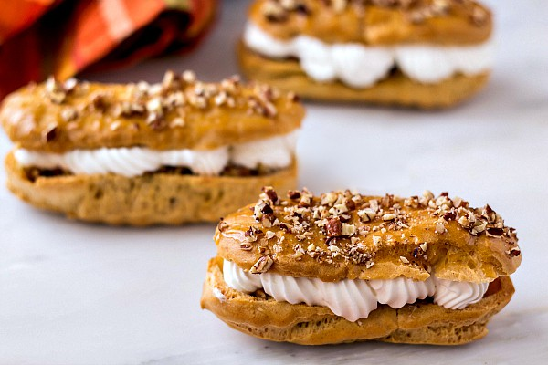 3 pecan pie eclairs with piped whipped cream and pecan pie filling
