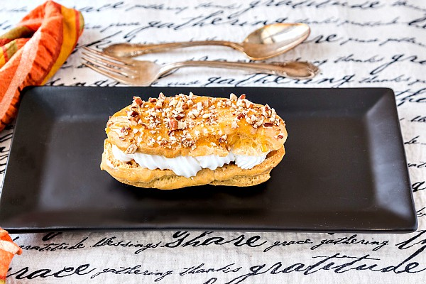 an eclair covered with chopped nuts on a rectangular plate