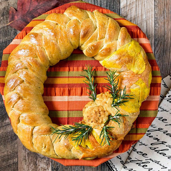 This Thanksgiving wreath braided bread centerpiece recipe only contains seven main ingredients, but wow, what an impact! And it's flavored with poultry seasoning, so it fits in beautifully with the rest of your Thanksgiving menu! #breadbakers | pastrychefonline.com