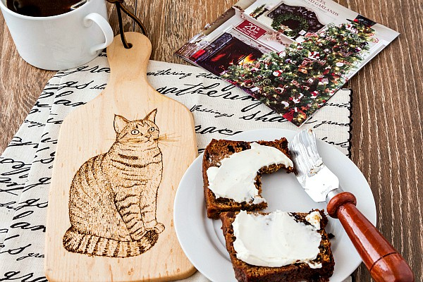 A cloth napkin and a small cutting board with an image of a cat and a plate with a slice of fruit cake with cream cheese on it