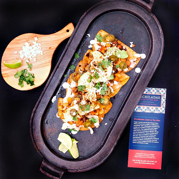 overhead shot of a platter of enchiladas, a cutting board with cotija cheese, a lime segment, and cilantro