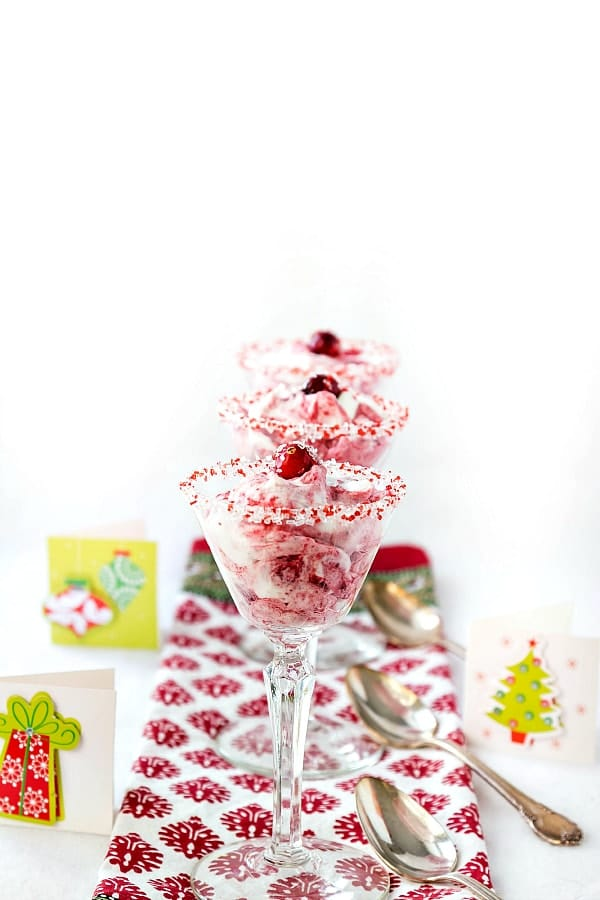 fruit fool made with whipped cream and cranberry sauce in cut glass wine glasses.