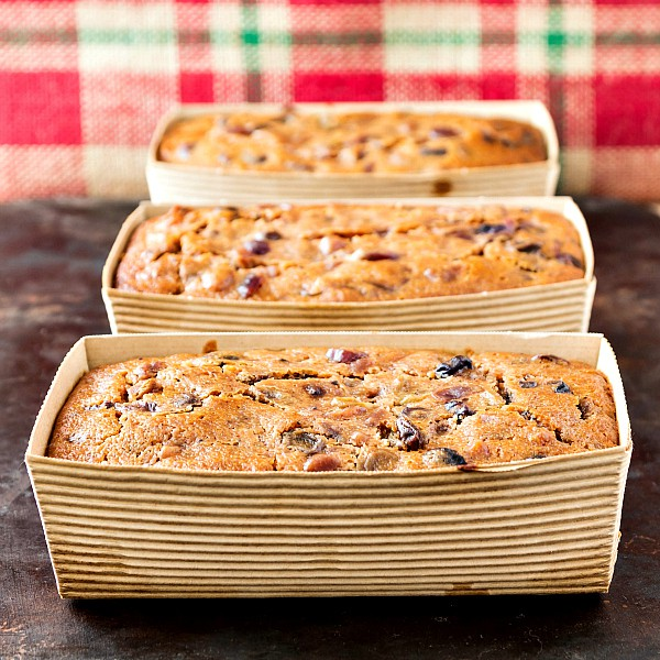 square image of three individual alton brown fruit cake in brown cardboard mini loaf pans on a brown surface with red and green plaid burlap in the background