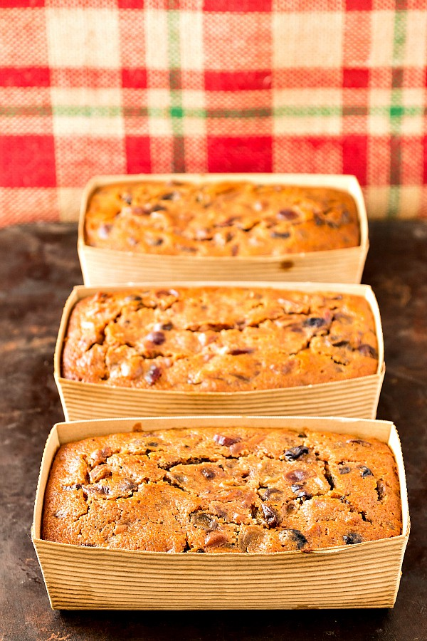3 individual fruit cakes in cardboard loaf pans with red and green plaid burlap as the background