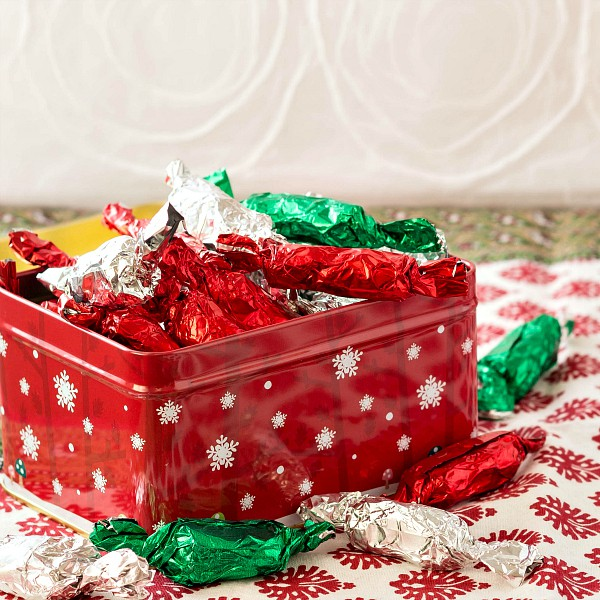 red metal box of chocolate pulled taffy wrapped in red, green, and silver foil