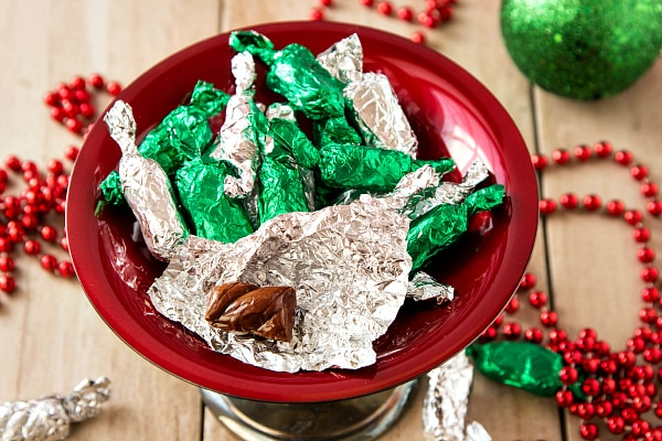 red candy dish of green and silver-wrapped taffy