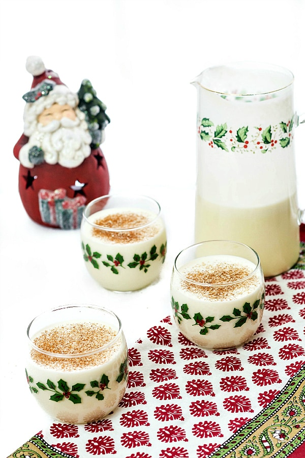 half-empty pitcher of eggnog with three glasses of eggnog topped with nutmeg