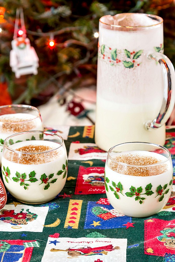 pitcher and glasses of eggnog with a christmas tree in the background