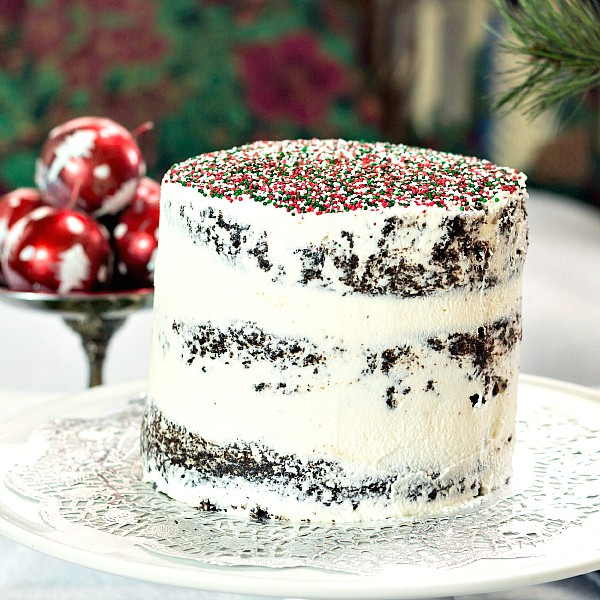 vegan christmas cake on a platter with red and green sprinkles on top