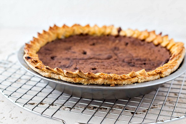 a whole chocolate chess pie in a metal pie pan cooling on a wire rack