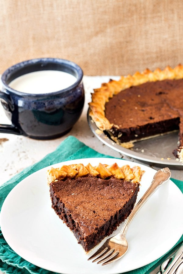 slice of fudgy chocolate chess pie on a white plate with the rest of the pie and a mug of milk in the background