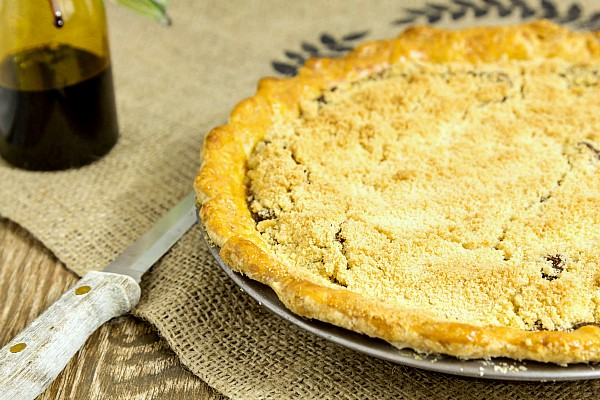 a whole baked shoo fly pie on burlap with a knife next to it