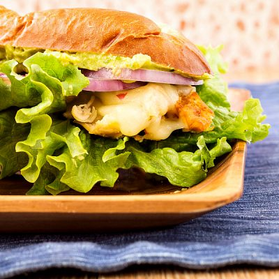a large sandwich on a plate with a lot of lettuce, cheese, and chicken