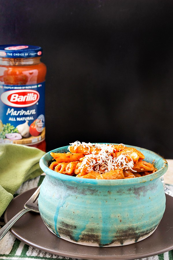a blue bowl of penne in a creamy sauce with a jar of pasta sauce in the background