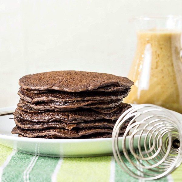 a plate of stacked chocolate yeast raised pancakes on a white plate with a whisk and some syrup in the background