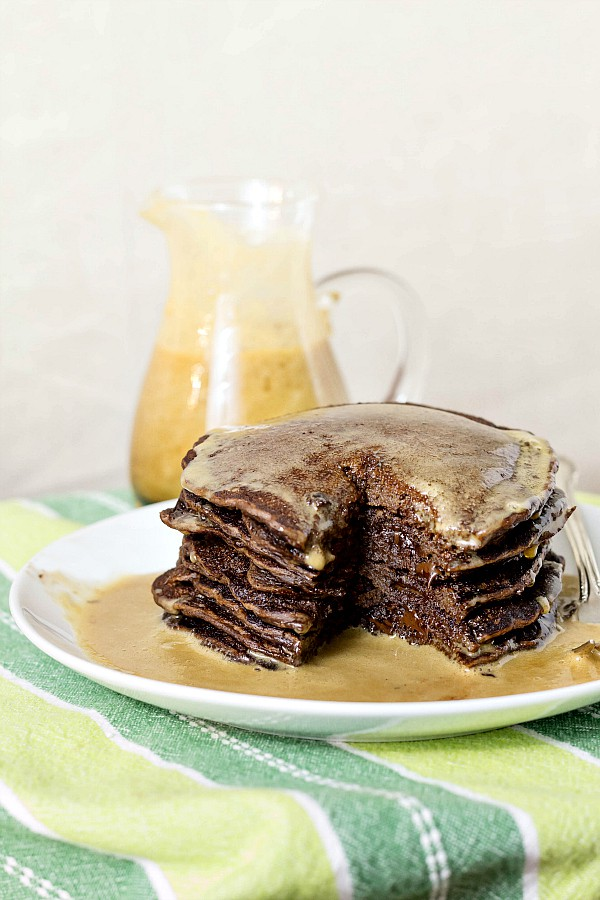 a tall stack of chocolate pancakes with chocolate chips on a white plate with syrup poured over them