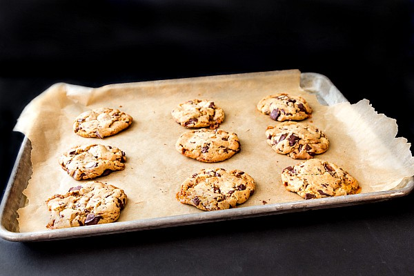 a parchment lined baking tray with baked cookies on it