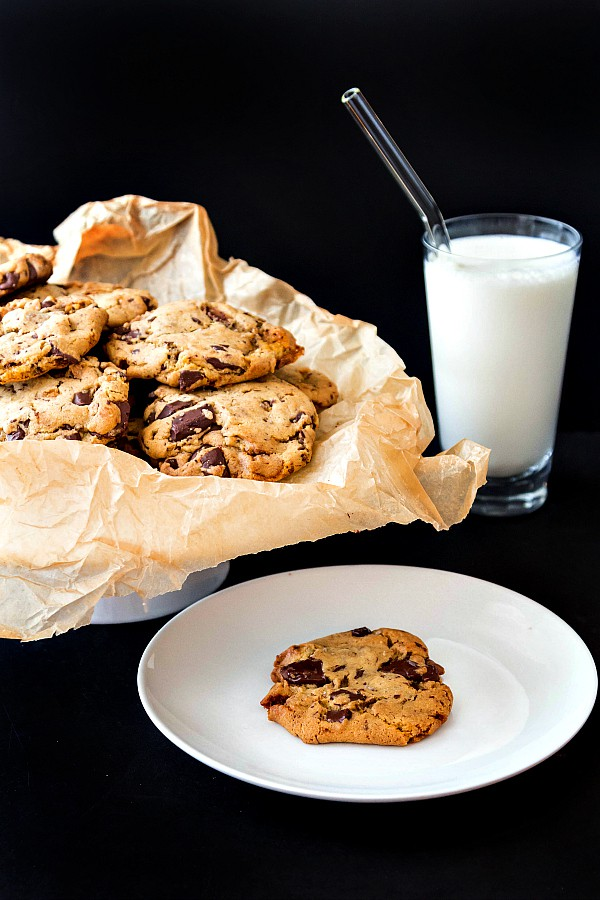 a plate of chocolate chunk cookies and a glass of milk