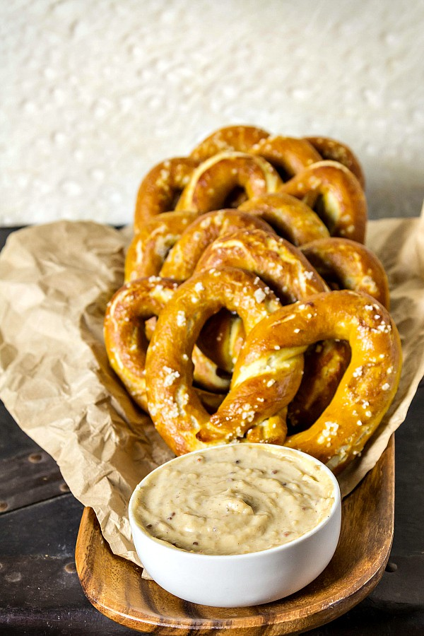 a wooden tray with salted softpretzels and beer cheese in a ramekin