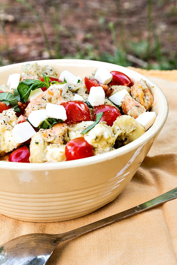 Enjoy this light and bright tortellini caprese salad. Sabra's Basil Pesto Hummus makes the perfect dressing base. Just add cooked tortellini, grape tomatoes, fresh mozzarella and basil and you are in business! Enjoy this pasta salad recipe for National Hummus Day on May 13 or whenever you need a light bite for your Unofficial Meal! | pastrychefonline.com