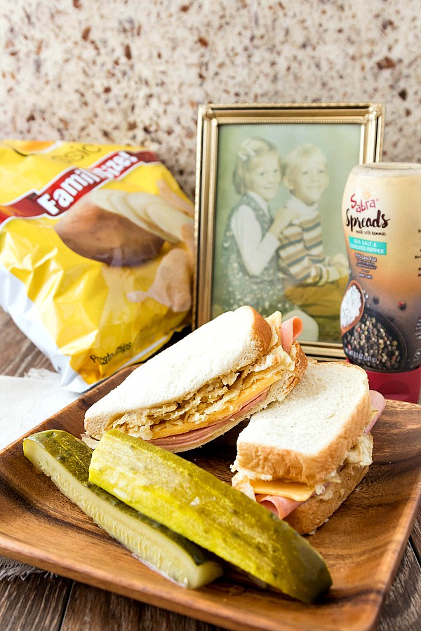 a bologna and cheese sandwich on a wooden plate with pickle spears and a bag of potato chips in the background.