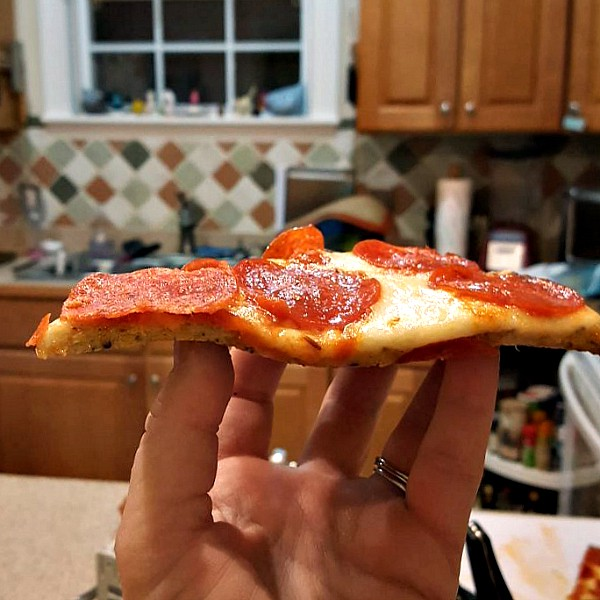 hand holding up a piece of pepperoni pizza made with cauliflower pizza crust