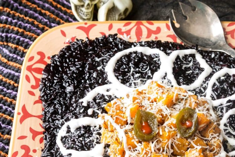 halloween risotto on a platter with butternut squash and small plastic skulls