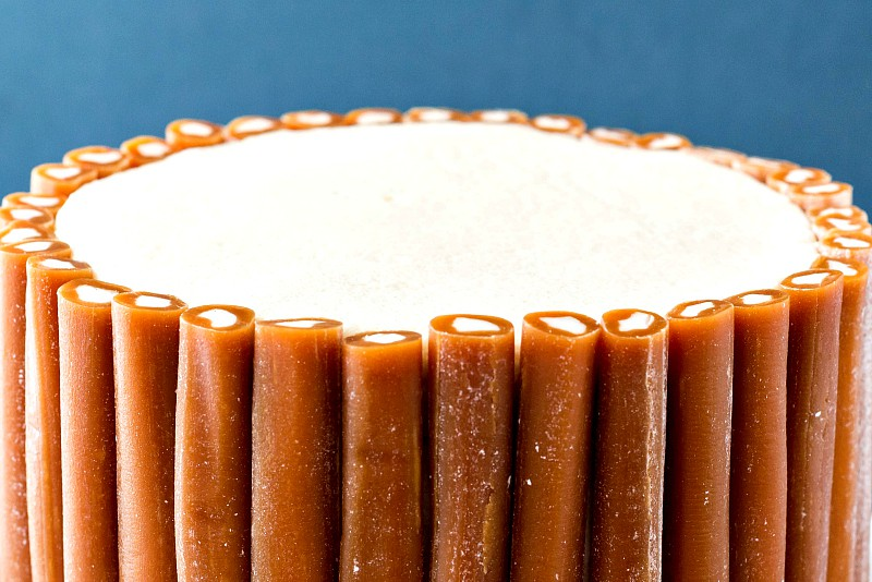 caramel cake with white frosting and Cow Tales caramels all around the sides