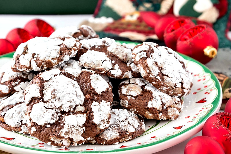 a pile of fudgy chocolate cookies coated in powdered sugar on a green and white plate