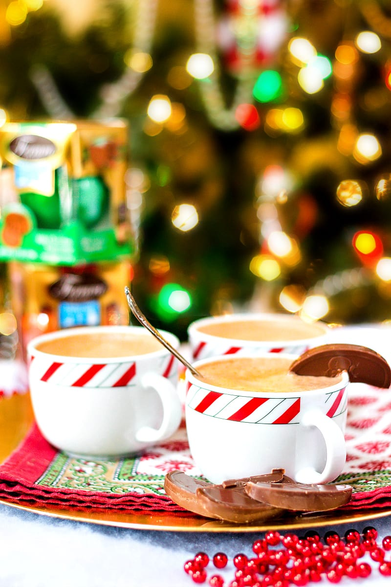 3 mugs of hot chocolate on a platter with a Christmas tree in the background