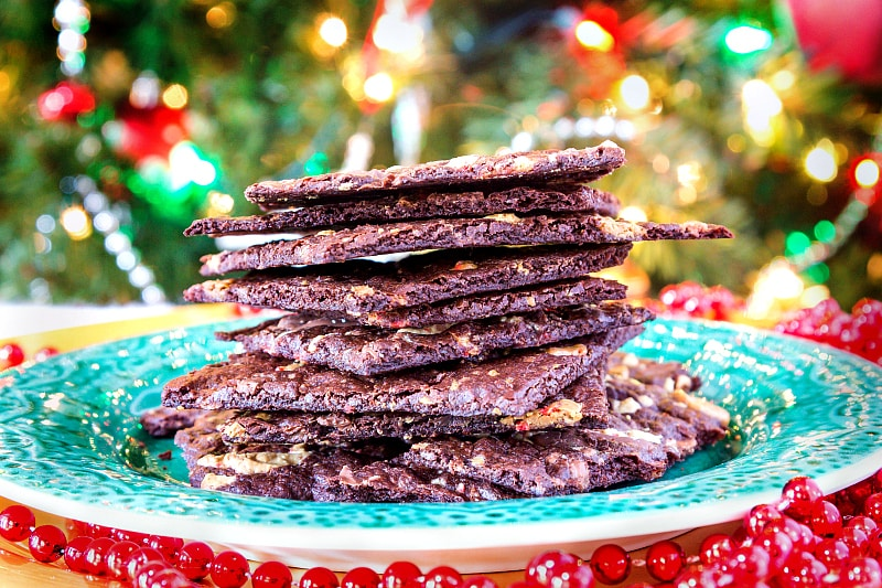 a pile of brownie bark from a peppermint brownie brittle recipe stacked on a green plate with a Christmas tree in the background
