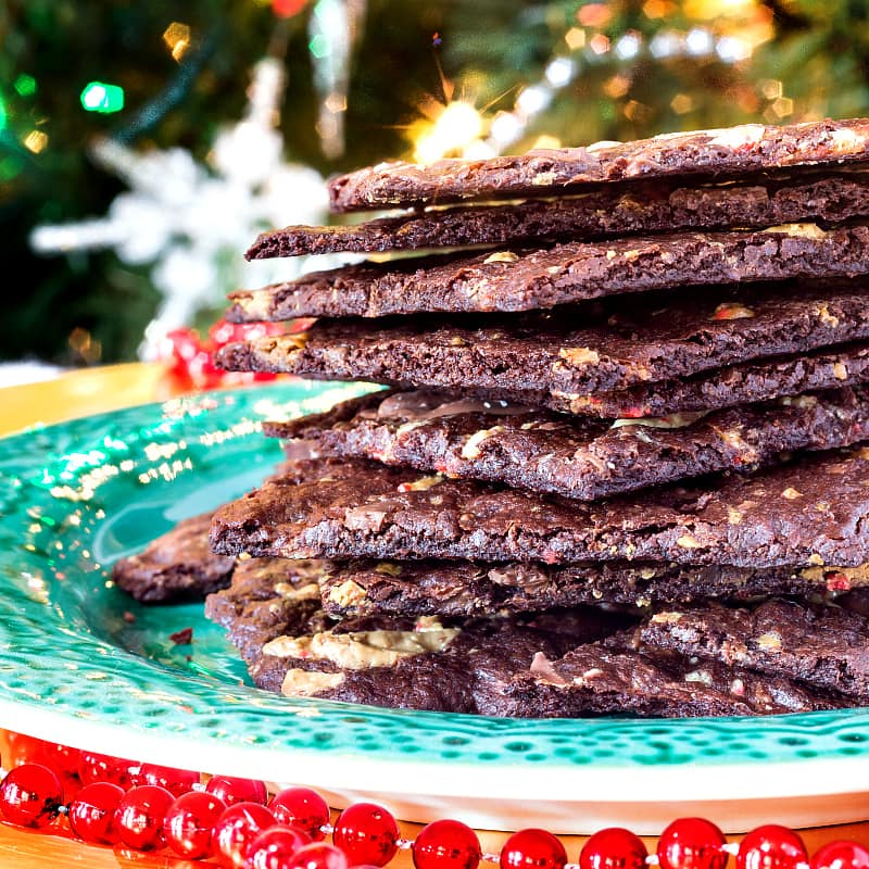stack of peppermint brownie brittle shot from the side on a green plate