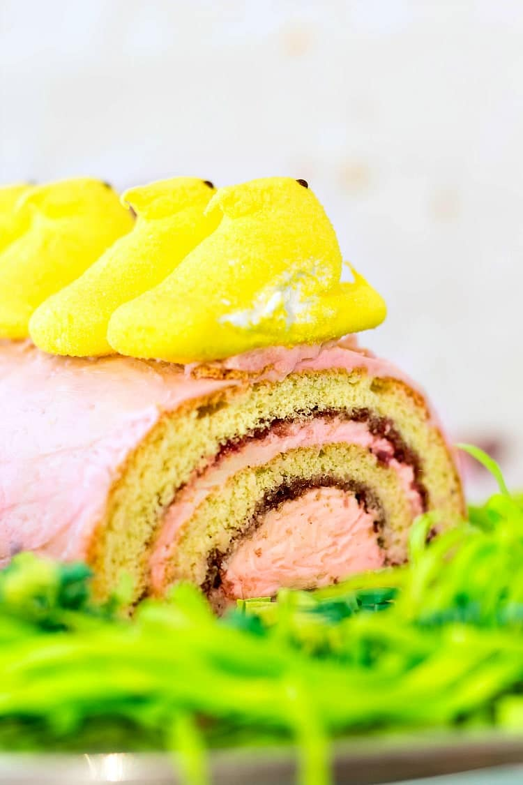 close up of a jelly roll with pink frosting topped with Yellow Peeps