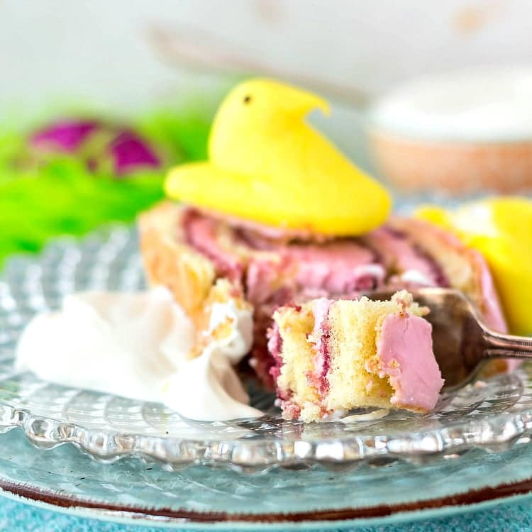slice of pink-frosted Peeps jelly roll with a bite on a fork, whipped cream on the plate and topped with a Yellow Easter peep