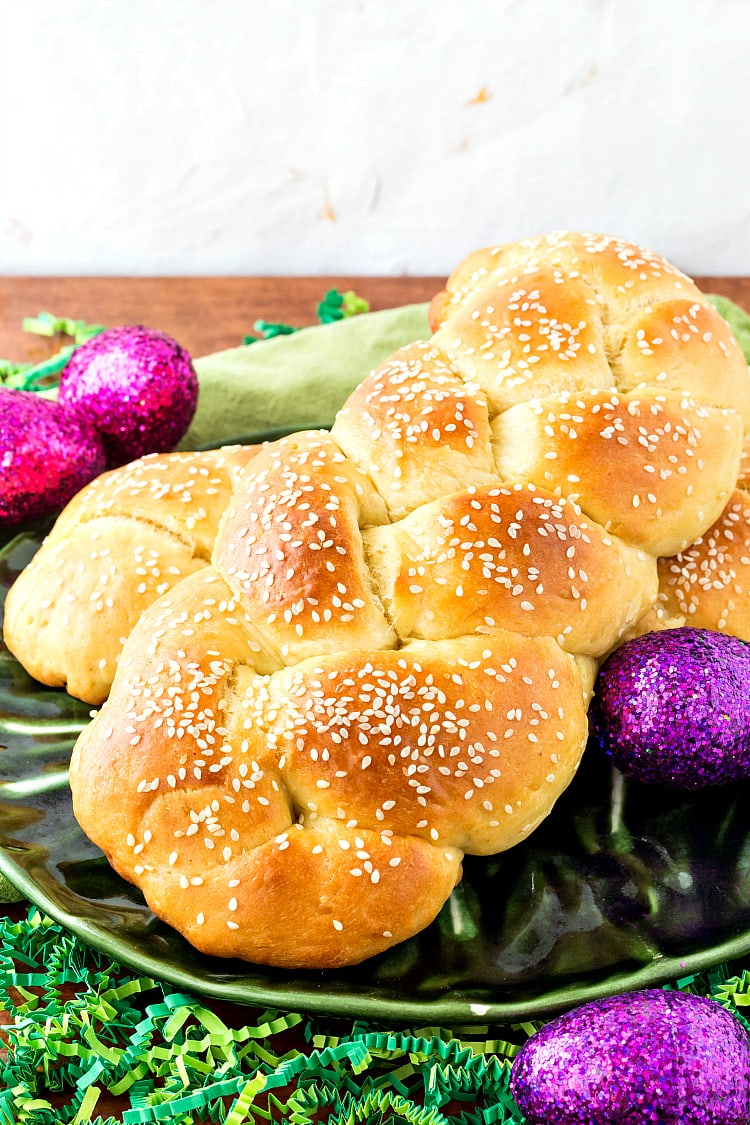 braided Armenian Easter bread or choereg on a green plate with glitter Easter eggs
