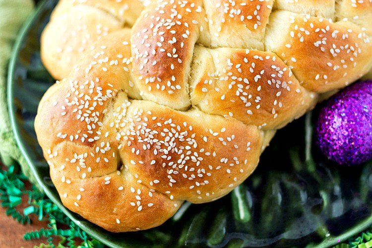 sesame seed-studded braided bread on a green plate