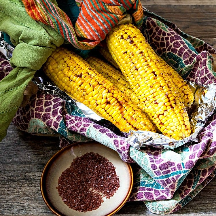 grilled corn in a basket with a plate of salt for serving