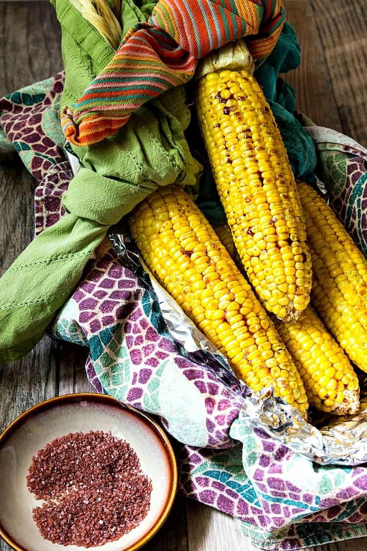 overhead shot of whole ears of roasted corn in a basket with a small plate of pink salt to serve with it