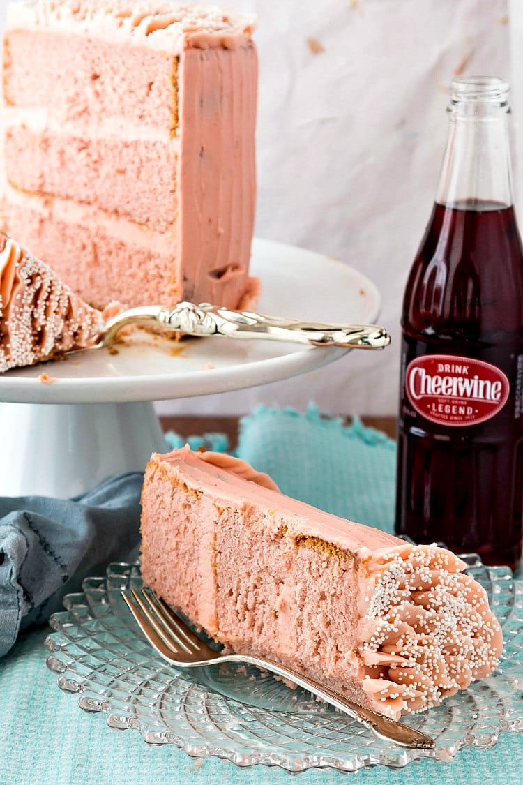 a slice of 3-layer pink cake with pink frosting with a bottle of Cheerwine and the rest of the cake on a platter