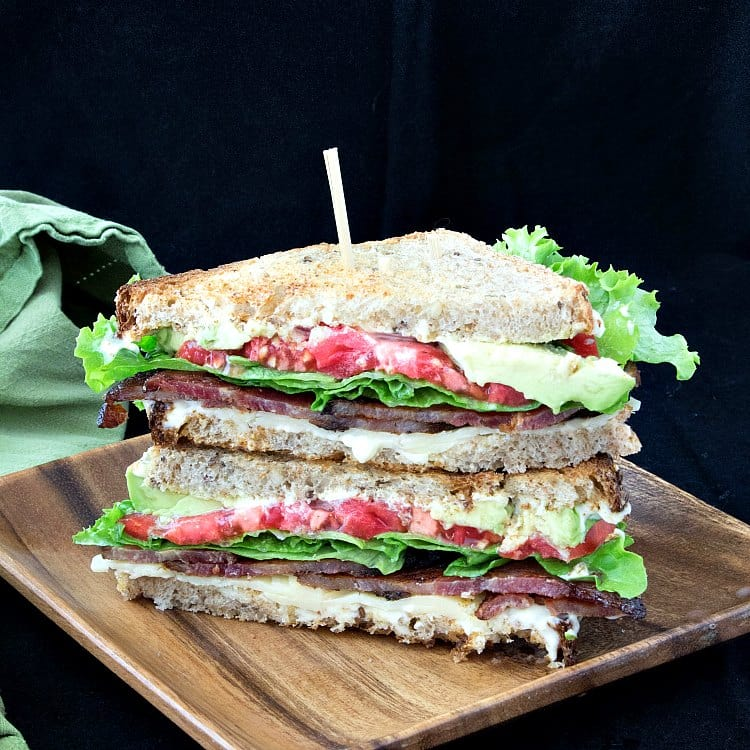 blt sandwich with cheddar and avocado sliced in half diagonally and stacked on top of each other on a wooden plate