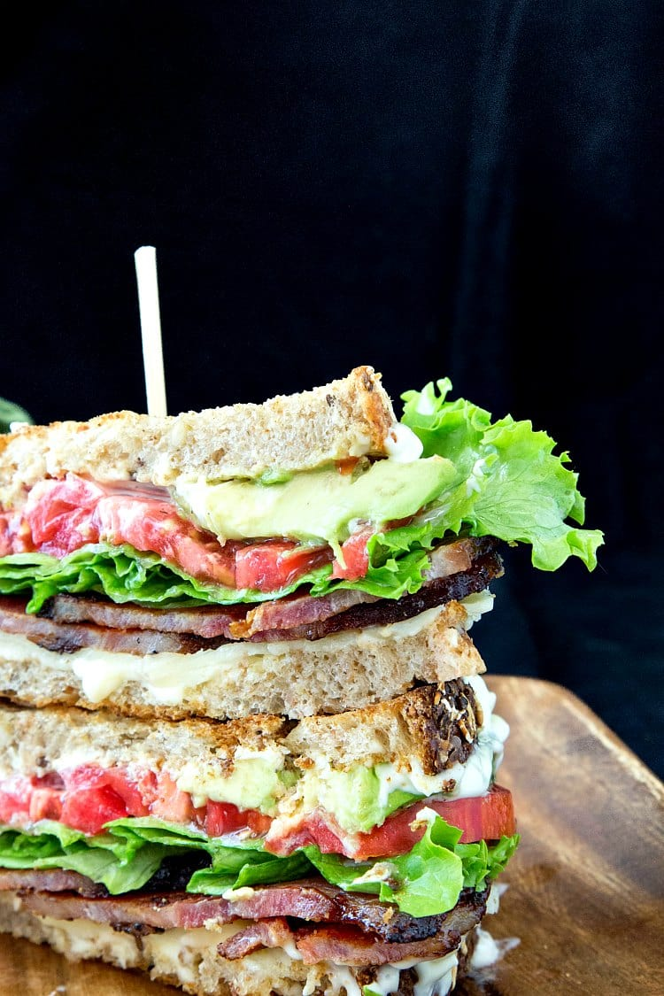 a blt sandwich cut and stacked on a wooden plate