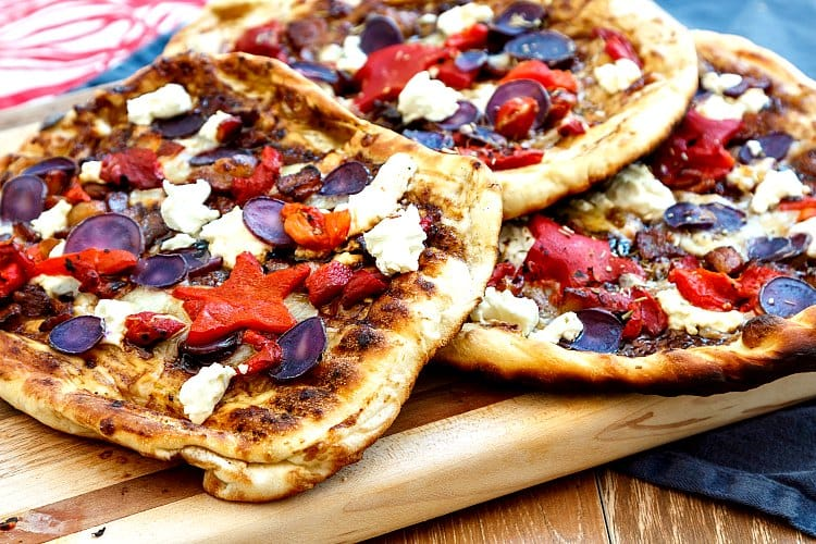 3 grilled pizzas with goat cheese, purple potatoes, and roasted red peppers on a wooden board