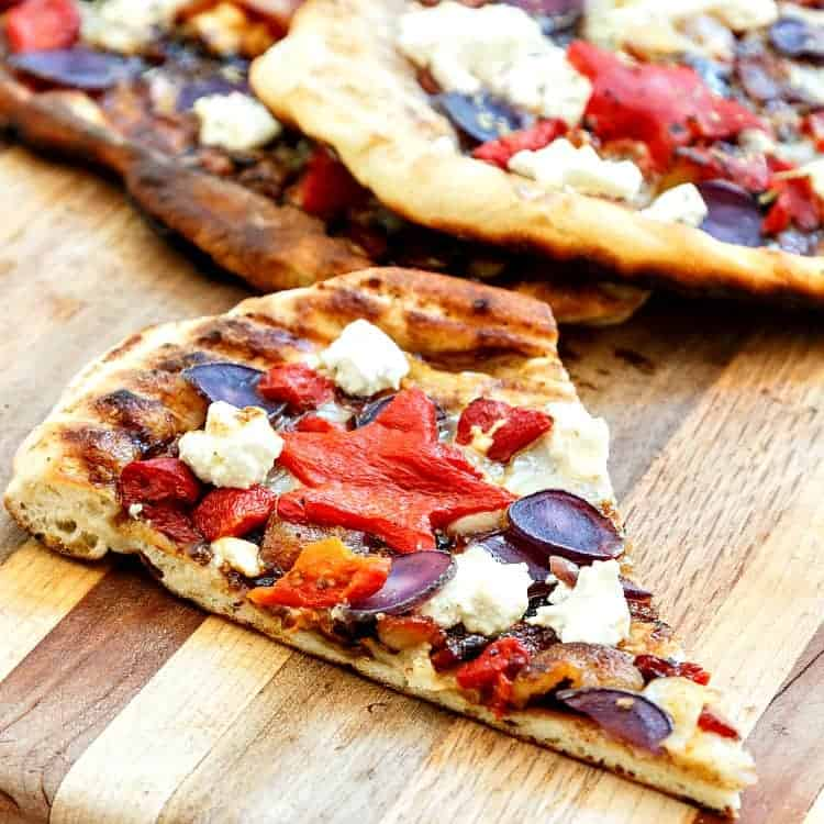 You don't need food dyes to make this grilled patriotic pizza. A base of fig, onion, and balsamic jam, some crisp bacon and grated mozzarella all topped with patriotic colors: sweet roasted red peppers (cut into stars, if you like), blanched blue potatoes, and creamy, white goat cheese. It's a fantastic combination, and perfect for your 4th of July cookout! | pastrychefonline.com