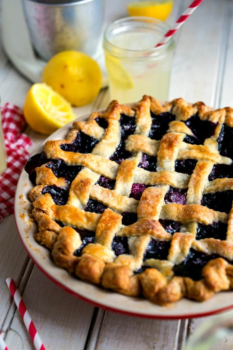 a lattice topped blueberry pie with a glass of lemonade with a straw in it, sliced lemons, and a red and white checked napkin