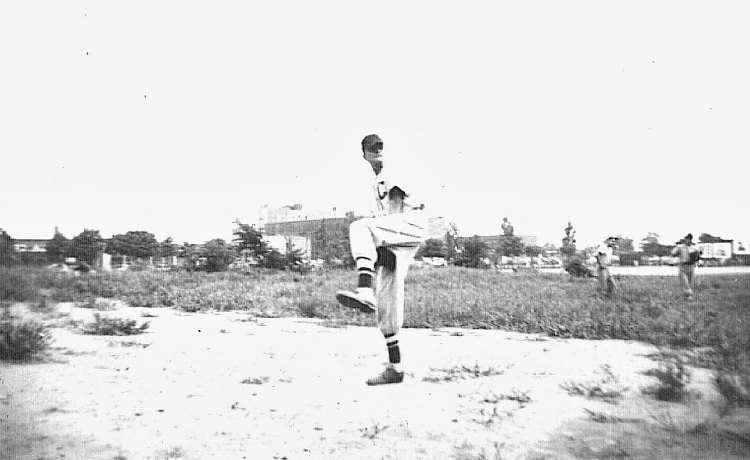 tall young man winding up to pitch during ball practice, mid-20th century Queens, NY