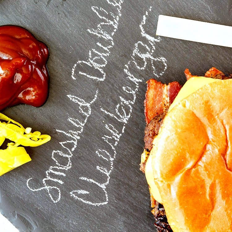 "An overhead shot of a burger and condiments on a piece of slate with ""smashed double cheeseburger"" written in chalk on the slate"
