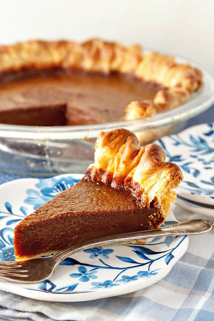 a slice of chocolate buttermilk pie on a blue plate with the whole pie in the background