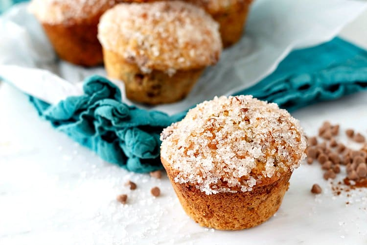 These double cinnamon raisin muffins have both ground cinnamon and cinnamon chips in them for extra cinnamon goodness. Their tops sparkle with coarse sugar--pretty enough for a fancy tea party, but just as at home in a lunchbox. You're going to love this cinnamon raisin muffin recipe for back to school or whenever you need a snack! | pastrychefonline.com
