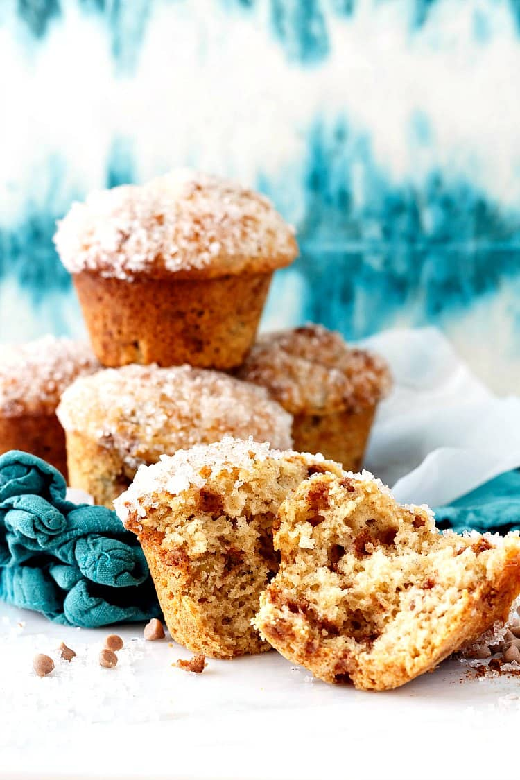 a pile of sugar-topped muffins. One in the foreground is split open to show the open crumb and cinnamon chips