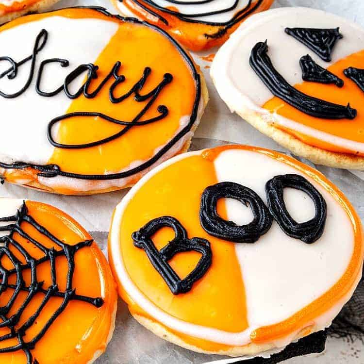 "black and white cookies decorated for Halloween in orange and white frosting with black designs. Cookie in front says ""Boo!"""